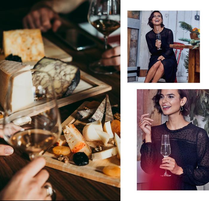 A couple enjoying a cheese board with glasses of white wine, & a woman in a black spot mesh dress holding a champagne flute.