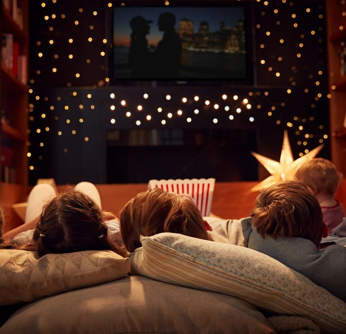 4 small children sitting on cushions watch in a movie on a TV on the wall.