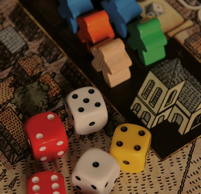 Five dice and a selection of carved wooden pieces laid out on a games board.