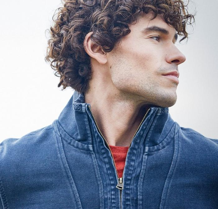 Close up of a male model wearing a navy and green half neck Airlie sweatshirt.