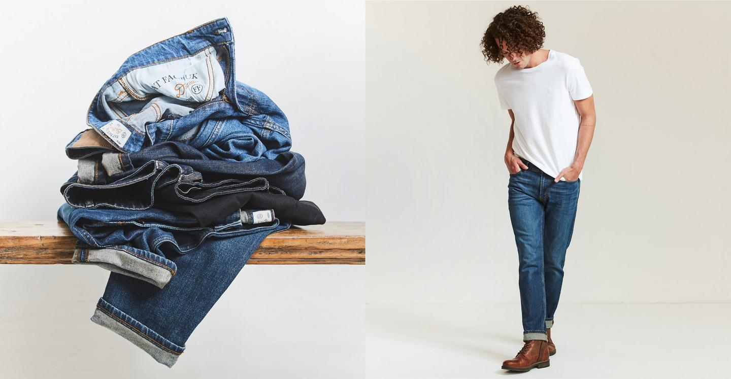 Man wearing a white T-shirt with mid-wash slim fit jeans, and a pile of FatFace denim jeans.
