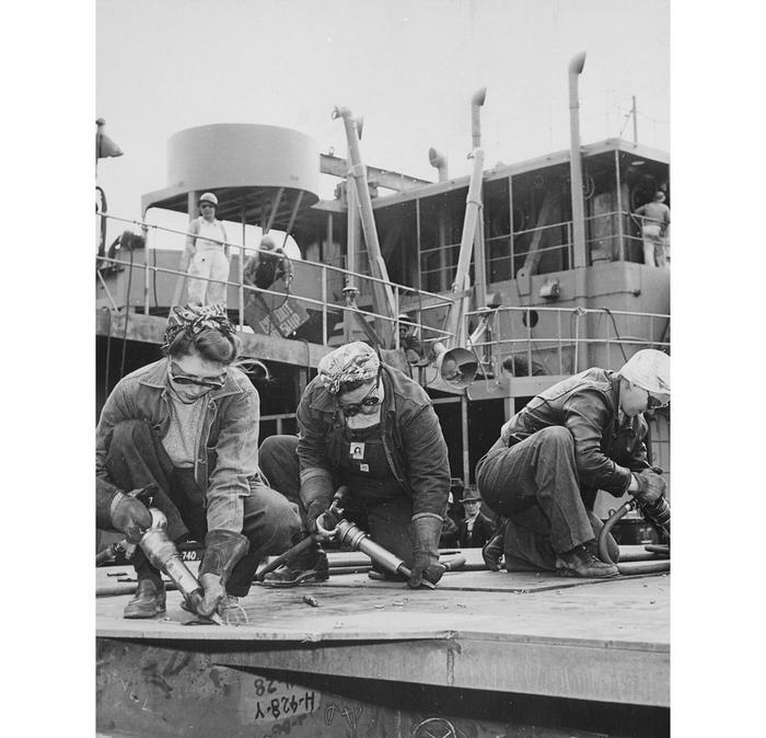 3 women in work overalls & welding goggles working on the deck of a ship.