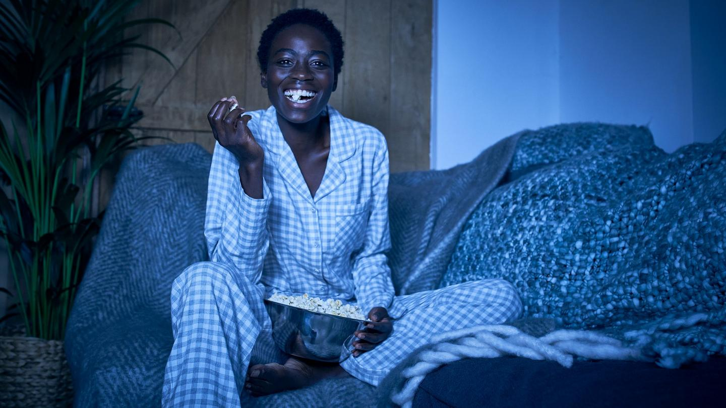 Woman wearing a grey & white gingham pyjama set, eating popcorn on a sofa draped in blankets.