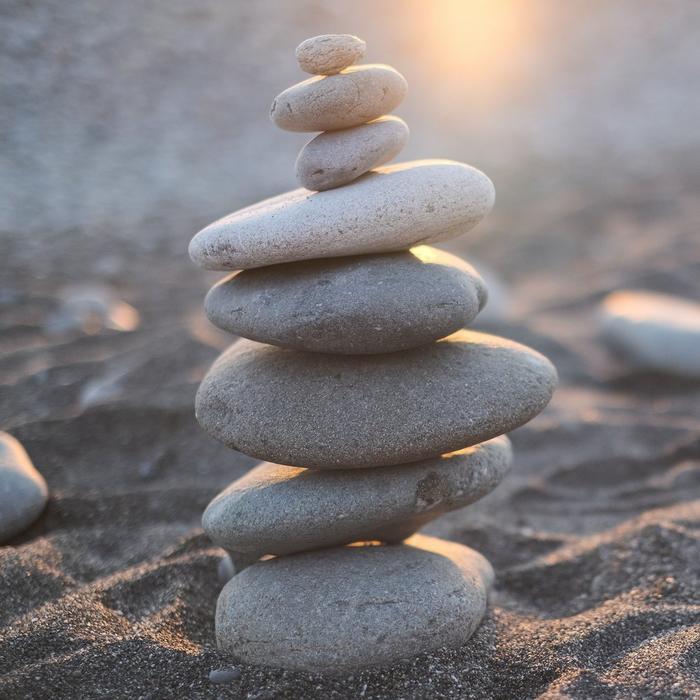 A stack of pebbles balanced in the sand.