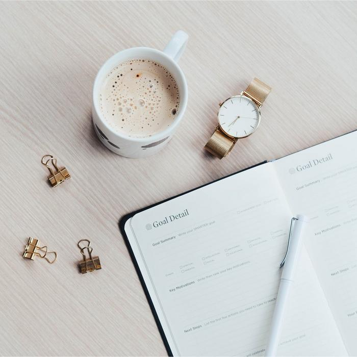 A diary, a watch, and a cup of coffee laid out on a table.