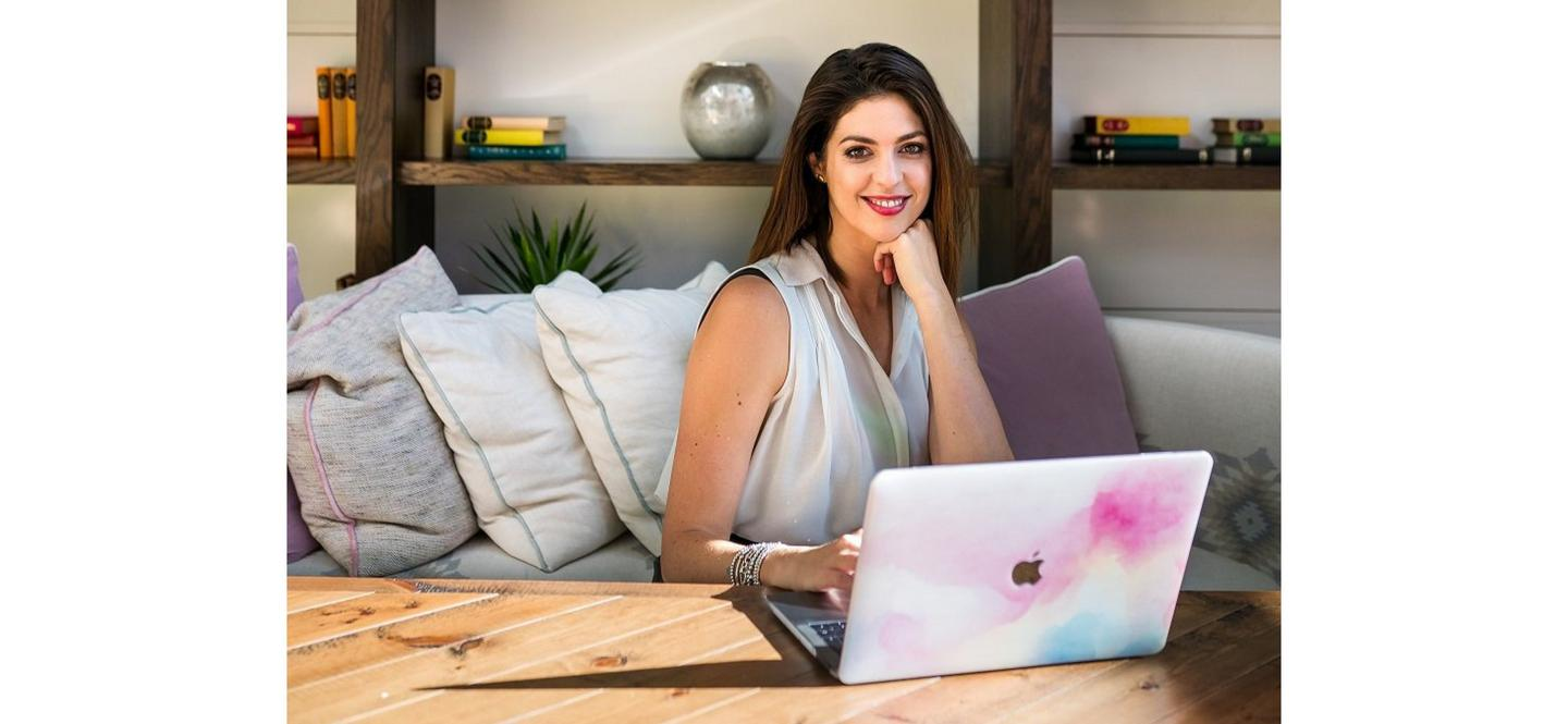 Psychotherapist Anna Mathur sitting in a brightly lit living room, working on a laptop.