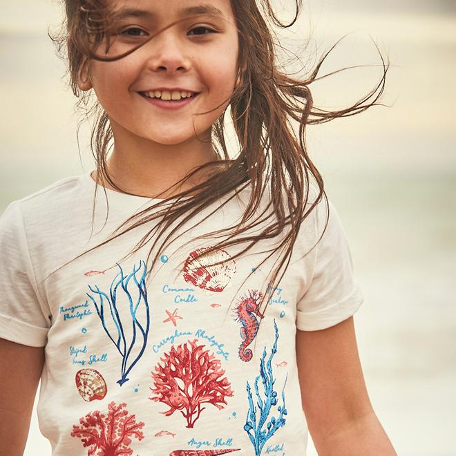 Girl wearing an ivory T-shirt with illustrated sea-life graphics.