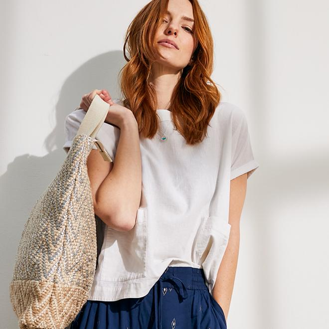 Woman wearing a white linen top with front pockets & navy linen trousers with embroidered pattern, carrying a large woven tote.