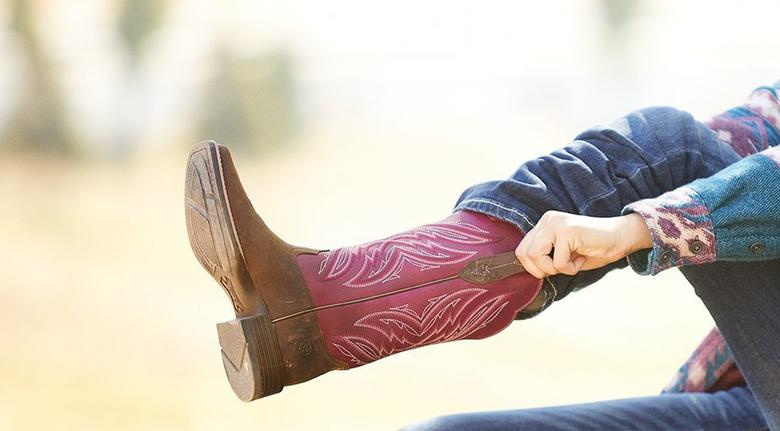 woman putting on cowgirl boots