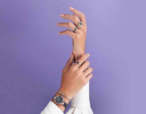 Sapphire rings on ladies hands. Wearing blue watch and white blouse