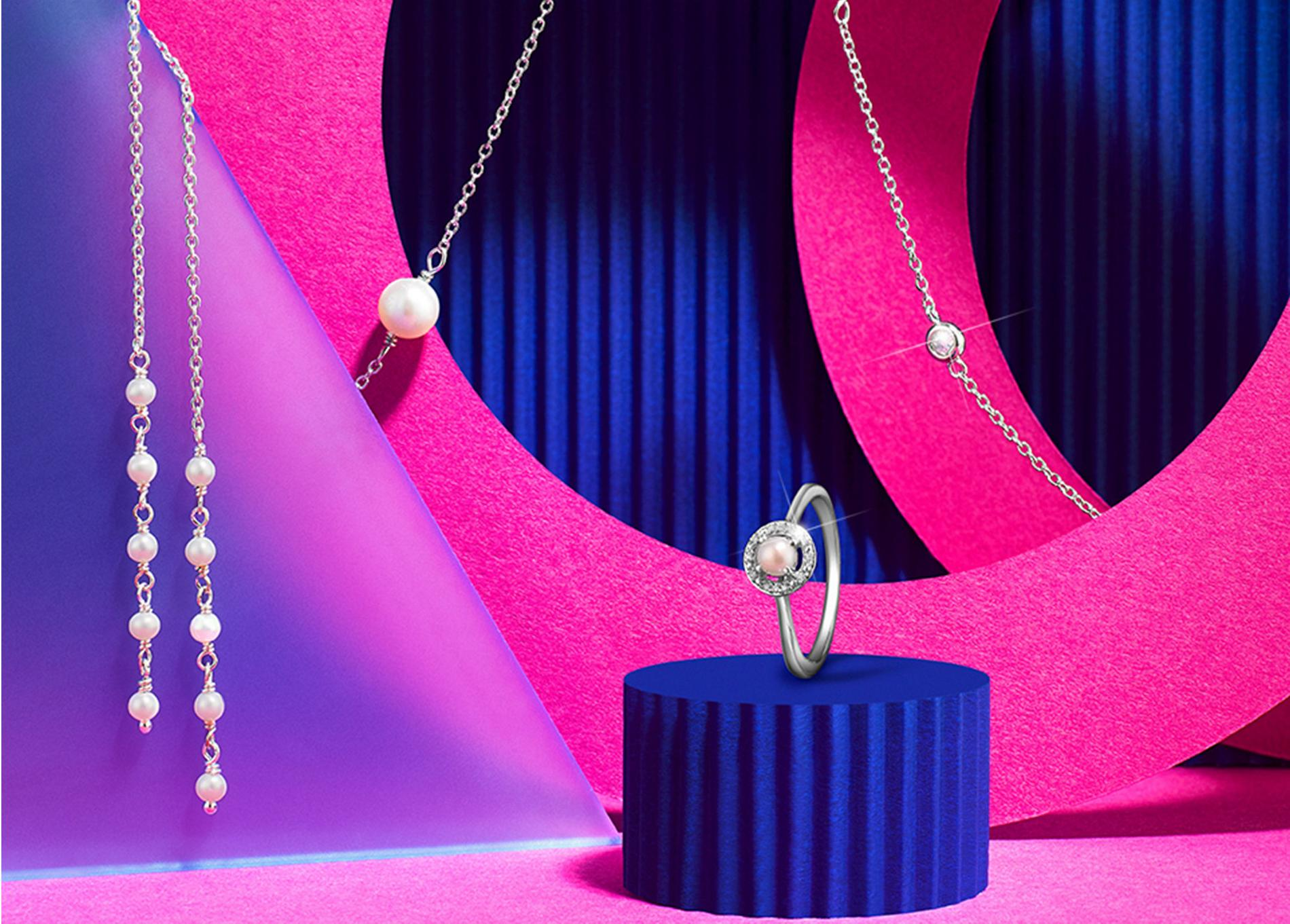 pearl jewellery against a pink and blue background